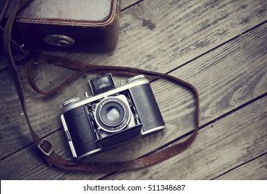 Old retro film camera and belt bag (leather case) on vintage wooden boards.