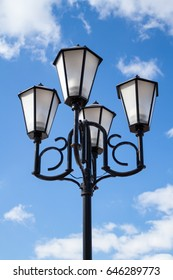 The old retro lamp post and the beautiful white and blue sky. Photo