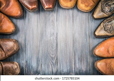 Old retro leather cowboy boots on aged textured wooden floor for background. Wild West nostalgic concept. Vintage style filtered photo