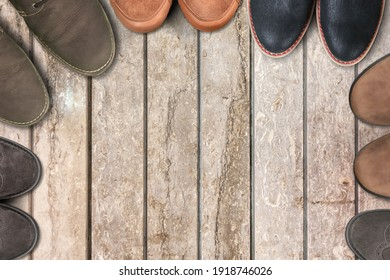 Old retro leather male boots on an aged textured wooden floor
