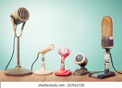 Old retro microphones for press conference or interview front mint green wall background