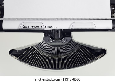 Old retro obsolete white typewriter with close-up typing text Once upon a time as heading on paper
