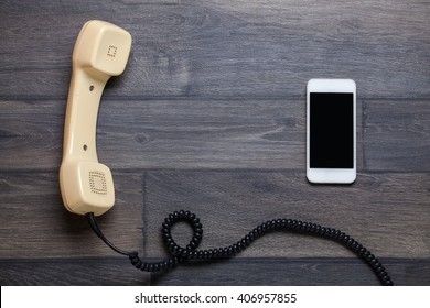 Old retro phone and new cell phone on wooden board, top view