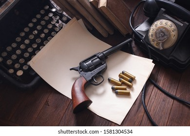 Old retro phone with vintage typewriter and a blank sheet of paper on wooden board with retro revolver gun