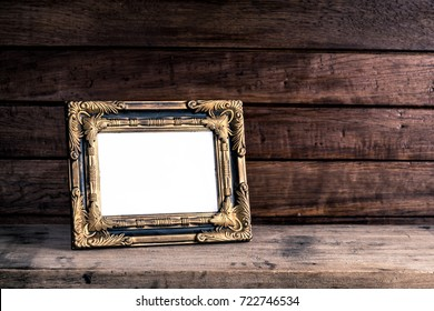 Old retro picture frame place on wooden table