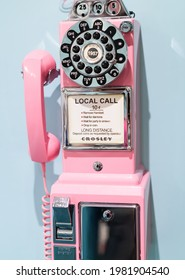 old retro pink wall phone on blue background