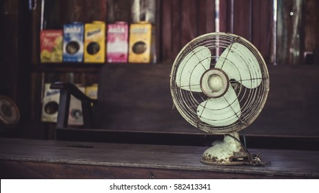 Old retro rusty grunge metal blades portable fan in vintage style photo.