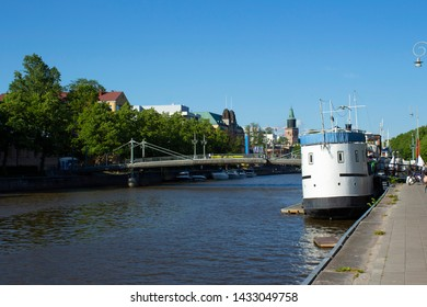 Old retro ship at the embankment of the Aurajoki river of the city of Turku and the view of the city of Turku in Finland on a summer day