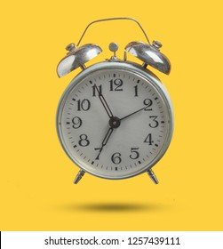 Old retro style alarm clock isolated on yellow background. 6:55 am. minimalism. Photo with shadow