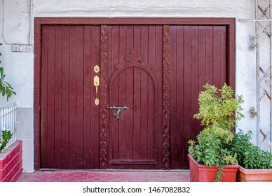 Old, retro style maroon hatch door with matching color wooden frame with intricate art craftsmanship. From Muscat, Oman.