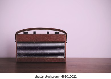 Old retro style radio on a wooden surface with light background Vintage Retro Filter.