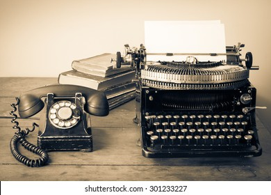 Old retro telephone, typewriter, books on table. Vintage style sepia photo