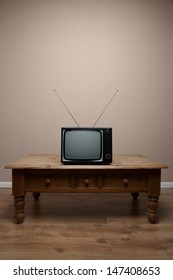 An old retro TV on a table with blank screen in an empty room, clipping path provided for the screen to add your own image or text.