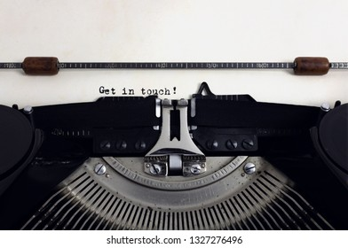 Old retro vintage black typewriter with close-up typing text Get in touch as heading on aged paper