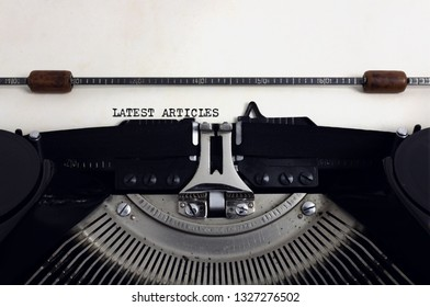 Old retro vintage black typewriter with close-up typing text Latest Articles as heading on aged paper