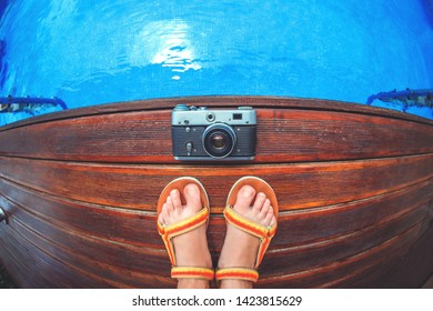 Old retro vintage camers and foot sandals standing on wooden sundeck near swimming pool. Flat lay style.