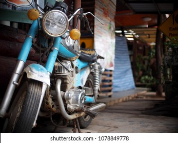 old retro vintage rustic abandoned blue colour motorcycle front wheel tyre with head and turn signal lamp closeup on old building wall selective focus blur background