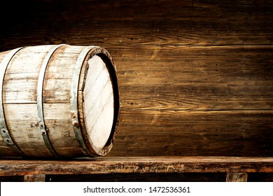 Old retro wooden barrel on desk and free space for your decoration. Dark wooden wall background and shadows.