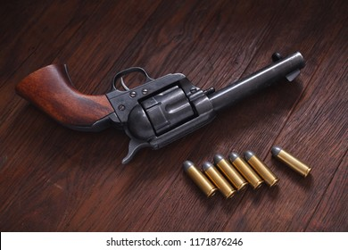 Old revolver with cartridges on wooden table