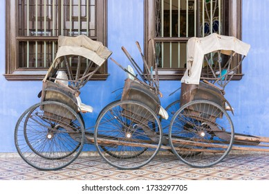 Old rickshaw standing against the wall of the Cheong Fatt Tze's Blue Mansion in Georgetown, Malaysia