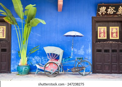 Old rickshaw tricycle near Fatt Tze Mansion or Blue Mansion, famous oriental historical building in Georgetown, Penang, Malaysia.