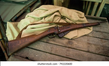 The old rifle lies on a wooden box. The rifle lies next to the burlap. The old rifle lies in the military bunker. Hostilities.