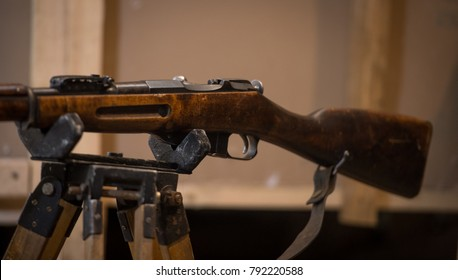 The old rifle is on the stand. The old rifle lies in the military bunker. Hostilities. The gun is on a blurry background.