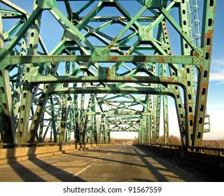 Old riveted iron bridge with rust and wear, illustrating aged bridges in the highway system.