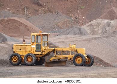 Old road grader in gravel pit.