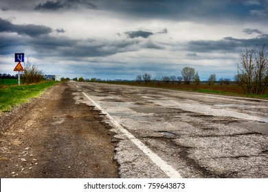 old road in potholes and holes outside the city in cloudy autumn weather HDR