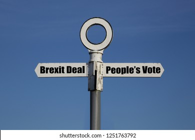 Old road sign with Brexit deal and people's vote on opposite sides against a blue sky