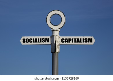 Old road sign with socialism and capitalism pointing in opposite directions against a blue sky