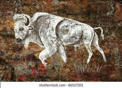 An old rock art drawing of a white buffalo painted on a rocky outcrop.