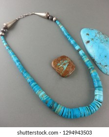 Old rolled handmade Navajo design Southwestern bright blue Turquoise Heishi beads necklace display with sterling beads strung up on old cotton string.
