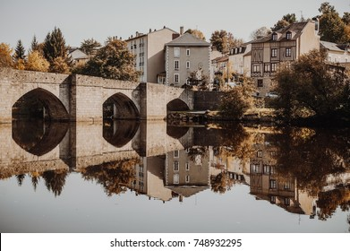 Old roman bridge with the symmetrical reflection on french riverbank with medieval buildings