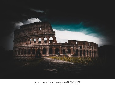 Old Roman colloseum amphitheater in Rome in grassy field under storm clouds for fantasy background