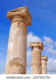 old roman columns in sunlight against a blue summer sky with clouds in kato park paphos cyprus