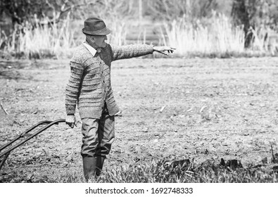Old romanian farmer on his sown land. Hand in air, looking around his fields. Vintage picture.