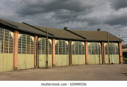 Old romantic storage building with huge doors and glass windows.