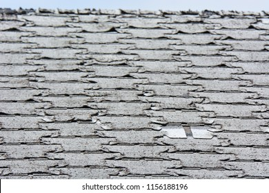 Old roof shingles in need or replacement with curled and missing tiles.