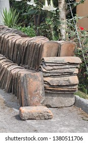 Old roof tiles piled on the side of a cobblestone street in Cotacachi, Ecuador