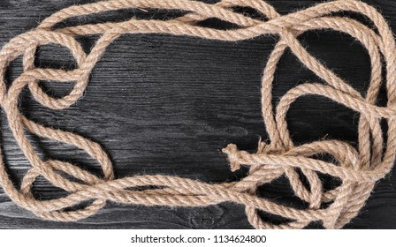 old rope closeup on black wooden background