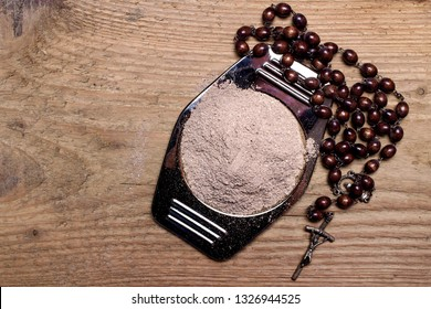 Old rosary and ash - symbols of Ash Wednesday. Top view