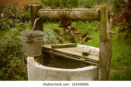 old rotten water well in summer garden, rural scenery
