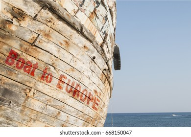 old rotten wooden hull with the words Boat to Europe, concept for the refugee crisis in the mediterranean sea