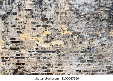 Old rough cracked wall constructed of gray bricks with concrete mortar, mold and peeled paint spots. Horizontal image suitable for interior design, backdrop, wallpaper. Template background.