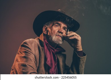 Old rough western cowboy with gray beard and brown hat smoking a cigarette. Low key studio shot.