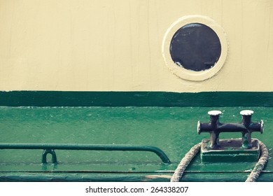 Old round porthole in gray ship hull and black mooring bollard on green deck, vintage toned photo with old style filter effect