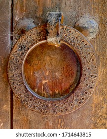 Old, round and rusty latch on a door at the entrance to a country house
