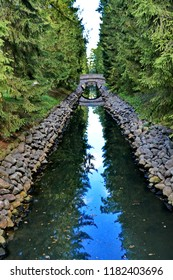 Old round stone bridge in the coniferous forest over a long narrow ditch with blue water between the stone walls in a beautiful city Park